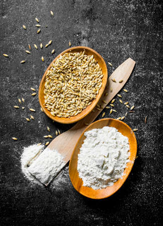Flour on a wooden spatula and bowl with grain. On dark rustic background