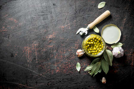 Canned green peas with Bay leaf and garlic cloves. On dark rustic background Stock Photo