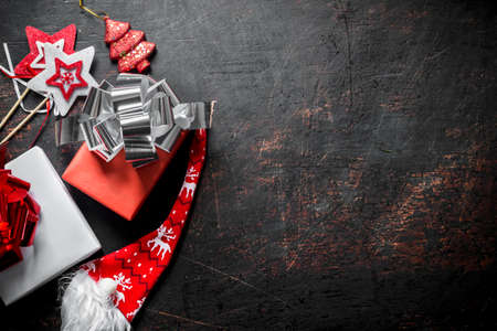 Christmas gifts in boxes with bows. On a dark rustic background