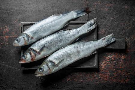Raw fish on cutting Board. On dark rustic background