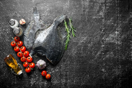 Raw fish flounder with cherry tomatoes, spices and garlic. On dark rustic background
