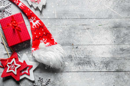 Red box with Christmas decorations. On white rustic background