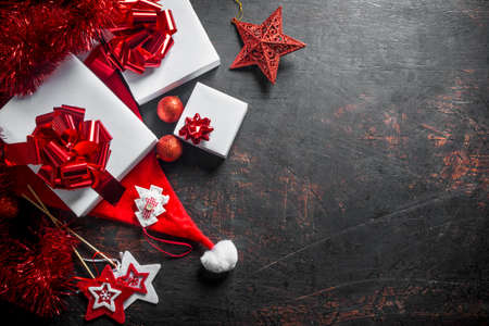 Christmas gifts with red Christmas decorations. On a dark rustic background