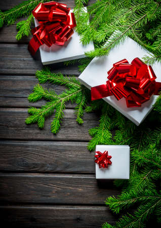 White Christmas boxes with green fir branches. On a dark wooden background