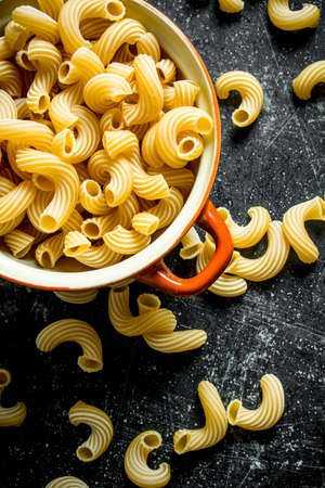 Pasta background. Dry the pasta in the pan. On black rustic background