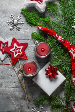 Christmas candles with gift box and fir branches. On white rustic background
