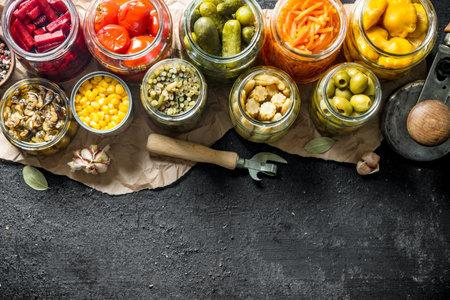Set of different pickled food. On black rustic background