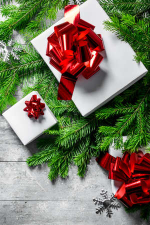 Gift boxes on Christmas tree branches. On white rustic background