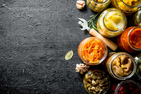 Jars of pickled food. On black rustic background Stock Photo