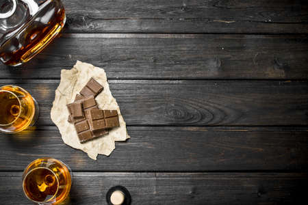 Cognac in glasses and a bottle of bitter chocolate. On black wooden background