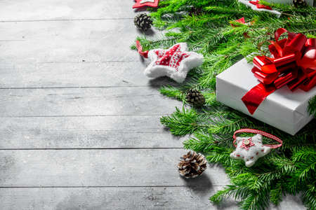 White gift box with Christmas decorations and fir branches. On white rustic background
