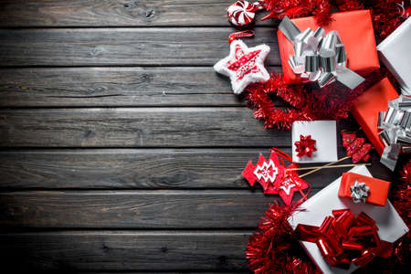 Christmas boxes with bows, decorations and tinsel. On a dark wooden background Zdjęcie Seryjne