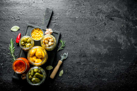 Preserved vegetables in jars on a cutting Board. On black rustic background