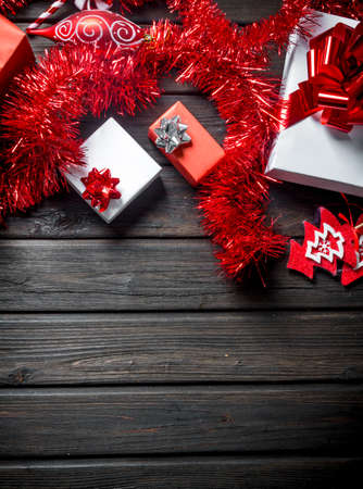 Various Christmas boxes with tinsel and decorations. On a dark wooden background