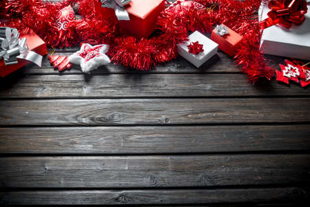 Red and white gift boxes with Christmas decorations. On a dark wooden background