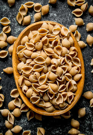 Pasta background. Dry pasta conchille in bowl. On rustic background