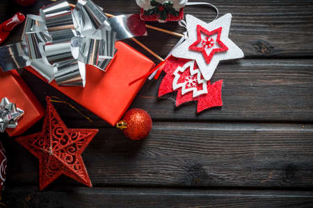 Red Christmas boxes with bow and Christmas decorations. On a dark wooden background