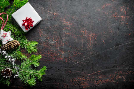 White gift box with Christmas decorations, fir branches and a cone. On a dark rustic background Zdjęcie Seryjne