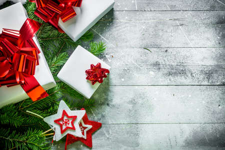 White Christmas gift boxes on spruce branches. On white rustic background