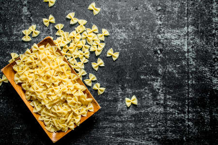 Dry Farfalle pasta on a plate. On dark rustic background