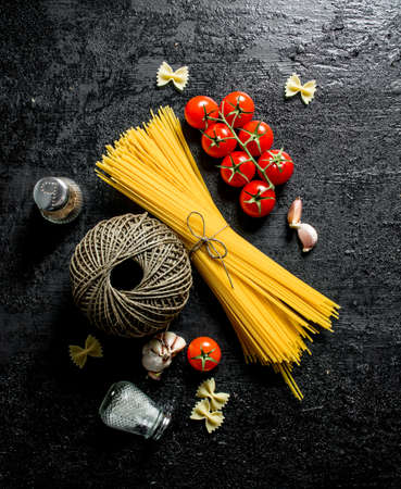 Raw spaghetti with tomatoes, spices and old thread. On black rustic background