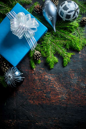 Blue gift box with Christmas tree toys and fir branches. On a dark rustic background Zdjęcie Seryjne