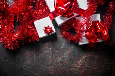 White gift boxes with red bows and Christmas tinsel. On a dark rustic background Zdjęcie Seryjne