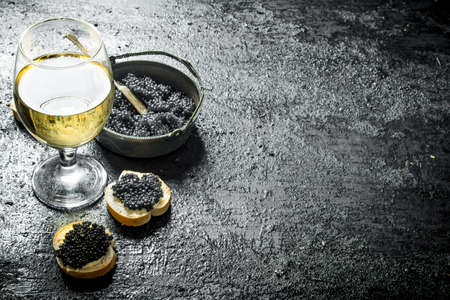 Black caviar in a bowl with sandwiches and wine. On black rustic background