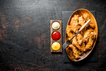 Chicken strips on a plate with a fork and different sauces. On dark rustic background