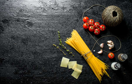 Raw spaghetti with twine, tomatoes and spice. On black rustic background