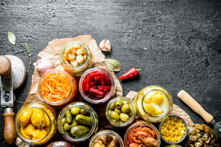 Assortment of different preserved food in glass jars on paper. On black rustic background