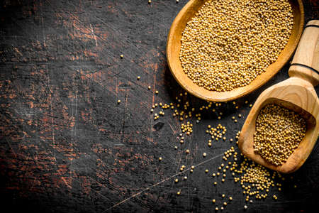 Dijon mustard in a wooden plate and scoop. On dark rustic background