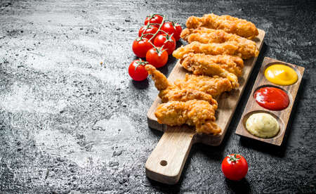 Chicken strips on a cutting Board with different sauces and tomatoes. On black rustic background