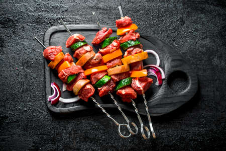 Raw kebab with vegetables on a cutting Board. On black rustic background Stock Photo