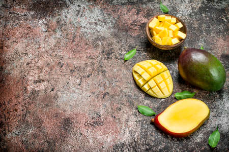 Pieces of ripe mango in bowl. On rustic background