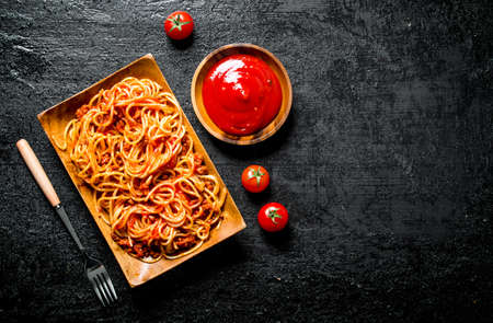 Spaghetti on a plate with tomato sauce in a bowl. On black rustic background