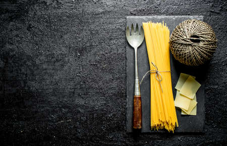 Dry spaghetti and lasagna with twine and lady. On black rustic background