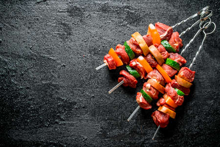Raw kebab with vegetables. On black rustic background Stock Photo