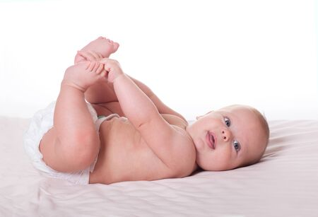 nude little girls: Cute happy baby boy girl kid lying and playing with its foot