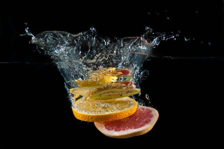 Tropical fruits fall underwater with a splash Stock Photo