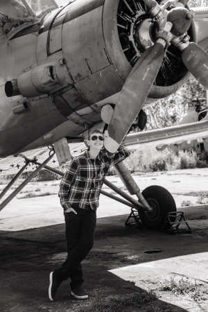 a boy stands near an old plane and thinks about flying when he grows up Reklamní fotografie