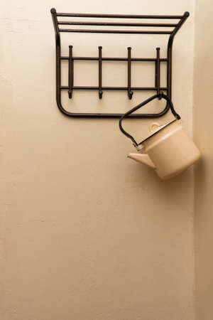an old yellow metal kettle hangs on the wall on an empty clothes hanger 版權商用圖片