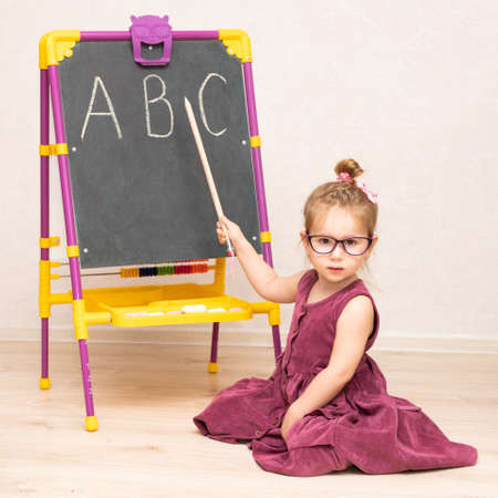 a little girl teacher in a dress and glasses sits on the floor near the blackboard and shows students the letters A B C of the alphabet.