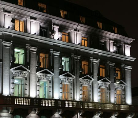 Lighting facade of goverment building at evening and its windows different color of light.