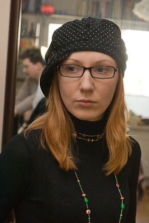 Young read-head woman in black cepy and black glasses. On background reflect of young man Stock Photo