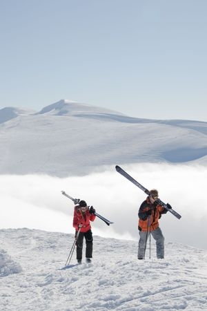 Young couple go up from a valley covered by a fog to top of mountain Stig for freeride. On a background the mountain Bliznitsa is shined by the sun.