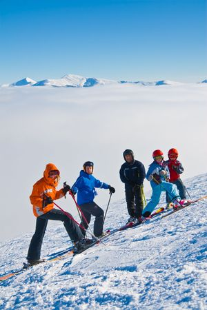 Group of children-mountain skiers on a slope of mountain Stig above a fog together with the trainer