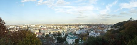 architector: View to the oldest historic district Podol of capital city of Ukraine Kyiv. On background new district of Kyiv on left side of river Dnipro. Right famous Andrew church (architector Rastrelli, 18 thentury).