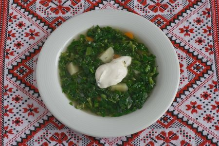 ukranian: The traditional ukranian season soup  is green borscht in a white plate on the embroidered cloth. Stock Photo
