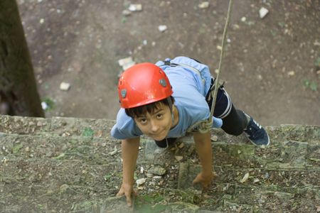Young boy train for climbing on old brick wall. View from the top.